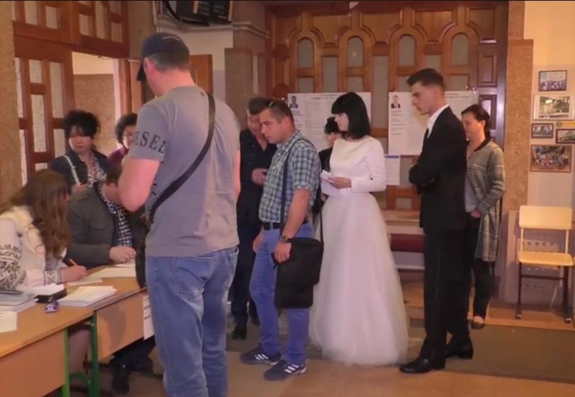 У весільній сукні і костюмі: в Ужгороді молодята після весілля прийшли голосувати
