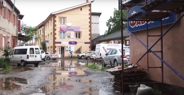 На одному з подвір'їв у центральній частині міста під час дощу утворються калюжі та бігають щурі